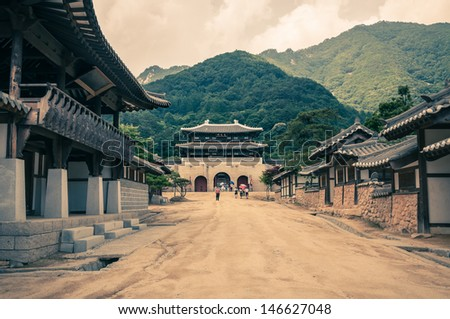 A long dirt road leads to an ancient gateway to this village in Asia. - stock photo