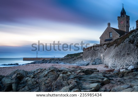 A long exposure at dusk of the clock tower at Porthleven a small fishing town in Cornwall - stock photo