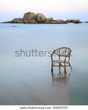 A long exposure beach with rattan chair. chair face to left side. chair position at bottom right. - stock photo