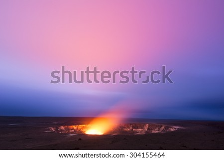 A long exposure during the early evening shows the glowing lava lake in the caldera of Hawaii's Kilauea Volcano as it bounces light off of the haze drifting by in the sky.  - stock photo