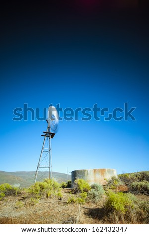 A long exposure image of a wind pump on a farm in an arid landscape