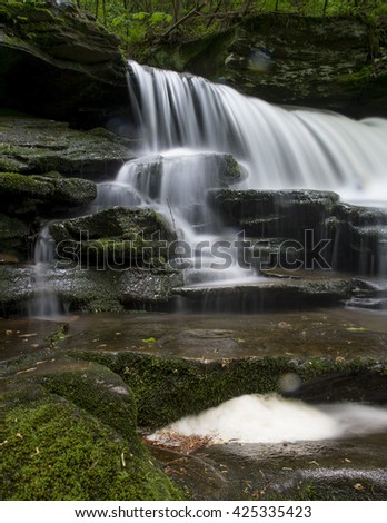 A long exposure of a scenic waterfall landscape in a bright green spring forest.