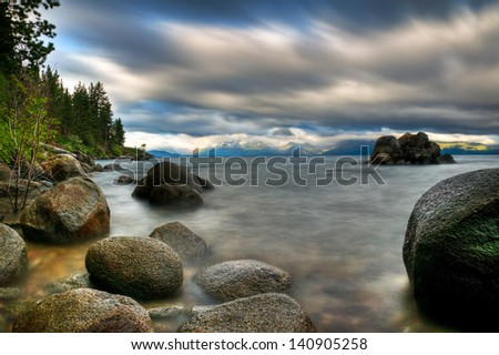 A long exposure of a stormy day on the rocky shoreline of Lake Tahoe.