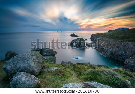A long exposure of a sunset over Lands End in Cornwall, looking out towards the Long Ships lighthouse - stock photo