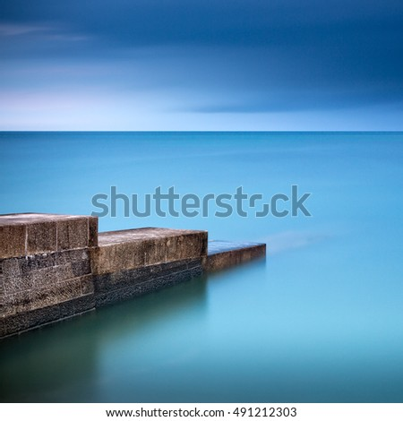 A long exposure of the the sea at Lyme Bay in Dorset England with a stone jetty leading into the sea.