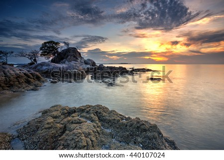 A Long Exposure Picture Of Beautiful Scenery Sunset With Big Stone As Background