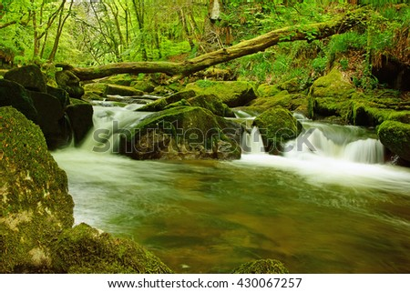 A long exposure view of the River Fowey flowing though Draynes Wood in Spring at Golitha Falls National Nature Reserve, Cornwall, England, UK