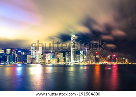 A long exposure view of the stunning Hong Kong island skyline taken from Kowloon, across the Victoria Harbor - stock photo