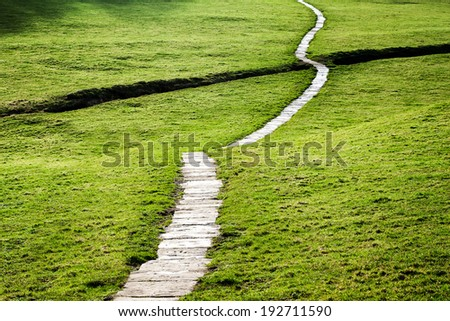 A long flagstone pathway snaking through a grassy field in the Yorkshire Dales, England, UK. - stock photo