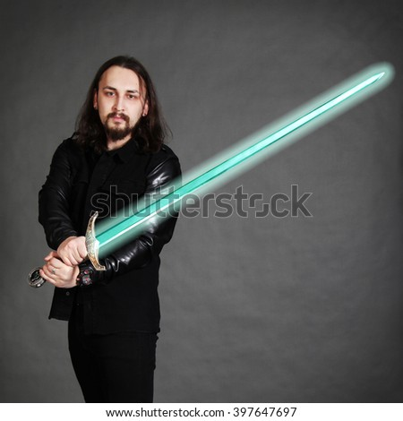 A long hair man with luminous sword on gray background