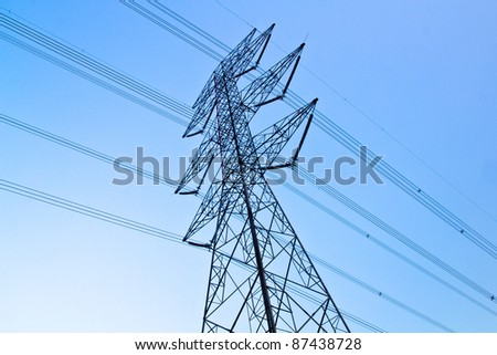 a long line of electrical transmission towers carrying high voltage lines. - stock photo