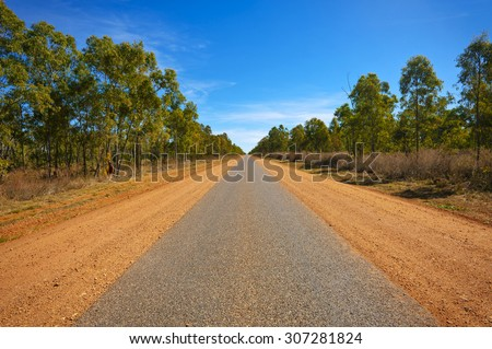 A long, narrow paved road in the Australian outback leads far into the distance. - stock photo