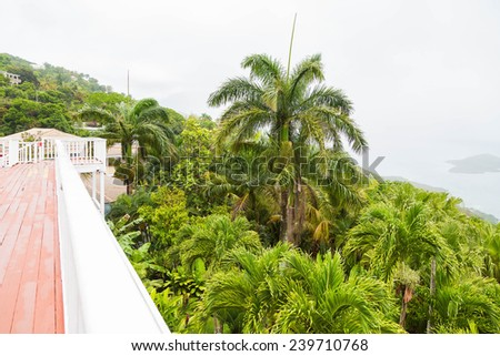 A long open veranda on a lush green hill over the bay off St Thomas - stock photo