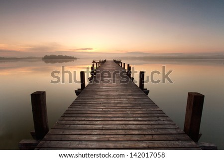 a long pier leading out onto the lake, sunrise on lake, long way out with fog - stock photo