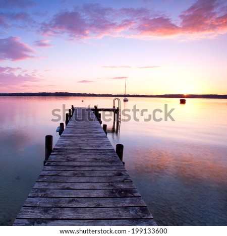a long pier leading out onto the sea, sunrise on sea, long way out  - stock photo