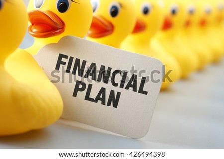 A long row of yellow rubber ducks with a sign that says Financial Plan on it.  - stock photo