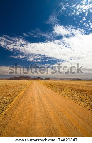 A long scenic gravel road in Namibia - stock photo