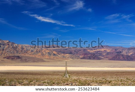 A long straight empty road travels through Death Valley National Park - stock photo