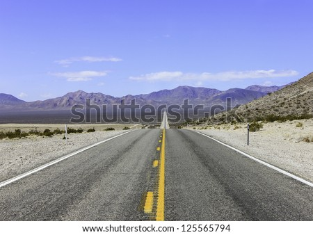 A long straight road in Death Valley with the desert and mountains in the distance - stock photo