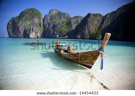 A long tail boat sits in Maya Bay, Koh Phi Phi Ley, Thailand. - stock photo