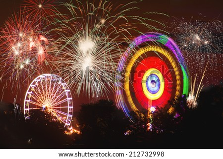 A long time Exposure of a big whell and a big carousell. With firework at the background. Picture is toned. - stock photo