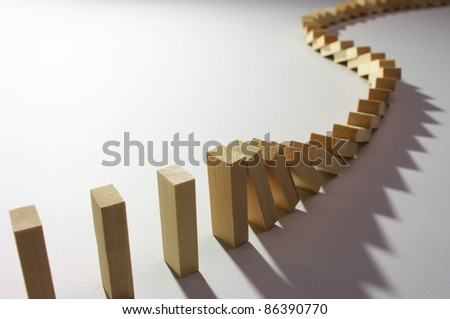A long train of dominoes falling over. - stock photo