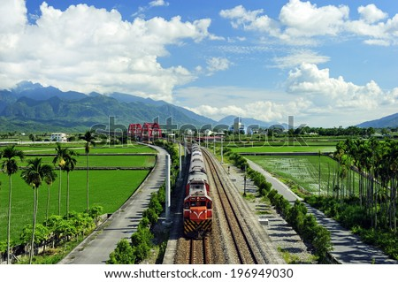 A long train on a railroad track on a sunny day.
