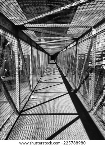 A long tunnel covered on all sides by wire fence. - stock photo