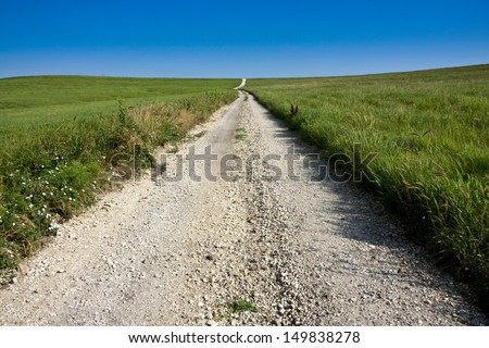 A long winding rural road in the Kansas Tallgrass Prairie National Preserve shows the depth and space of the green pasture and tall grassland available in this preserve. - stock photo