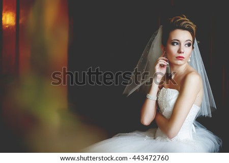 A look from a far on a thoughtful bride sitting in the dark room