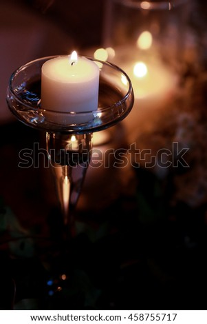 A look from above on a tiny candle burning over the daisy wreath