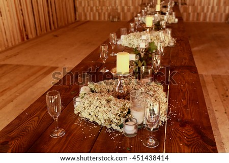 A look from above on the wooden table full of white flowers and candles - stock photo