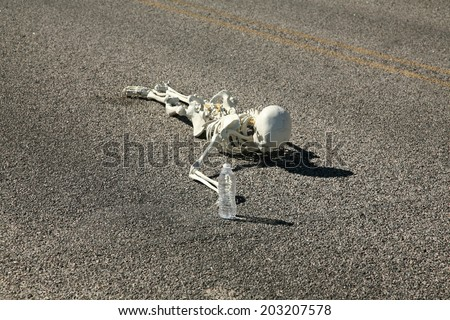 A lost hiker dies of thirst on a deserted desert road inches away from a bottle of water.  Dark Humor Series.  - stock photo