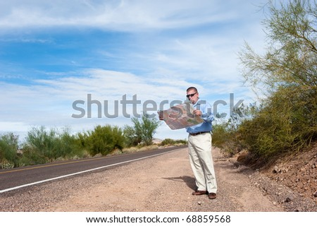 A lost man stands alone on a deserted road reading a map. - stock photo