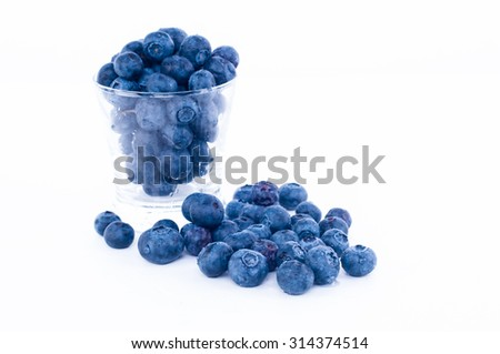A lot blueberry fruit in the glass and outside from glass with white background ( shallow depth of field) - stock photo