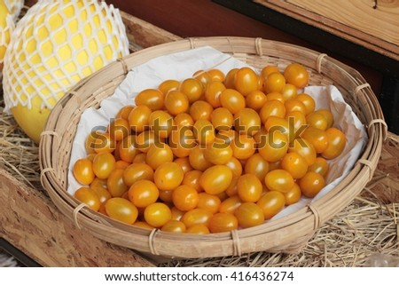 A lot fresh yellow tomatoes in basket