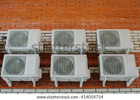 a lot of air conditioners on a brick wall