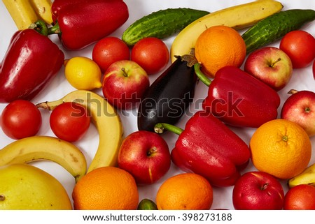A lot of beautiful vegetables and beautiful fruit are spread out on a white background