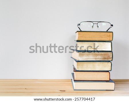 A lot of books for studying and black glasses