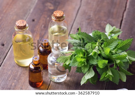 A lot of bottles with essential aroma oil with mint on wooden background. Selective focus. - stock photo
