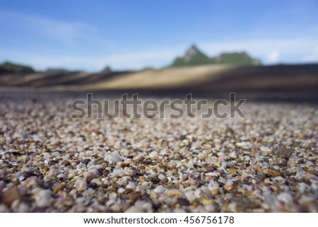 a lot of broken small corals, scrap of sea shell on the sand on foreground and blurred blue sky and mountain in background,filtered image,selective focus - stock photo