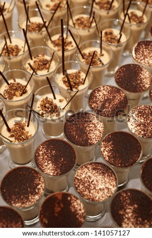 A lot of chocolate desserts in shot glasses, close-up