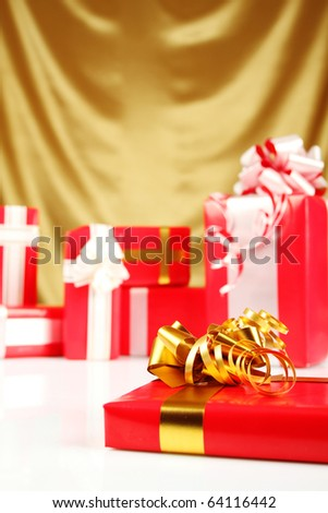A lot of Christmas presents different values in the red packages with colorful bows on a gold background