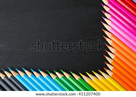 a lot of colored pencils closeup on wooden background form an angle - stock photo