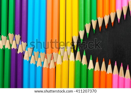 a lot of colored pencils closeup on wooden background laid out in the form of a snake - stock photo