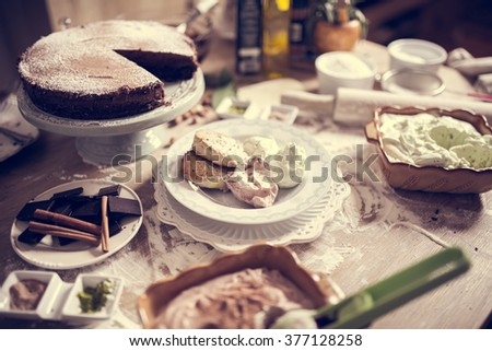 A lot of desserts on the kitchen table.Celebration,holiday sweet food.Birthday feast.Catering food,service.Cafeteria,restaurant kitchen.Homemade desserts,ice cream,chocolate cake and cookies.Recipes - stock photo
