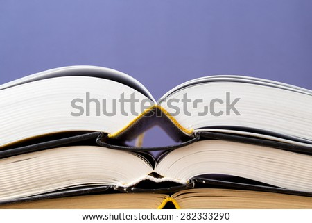 A lot of different books are opened and lie on top of each other on a blue background - stock photo