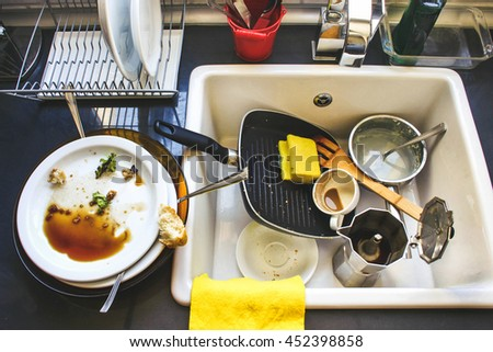 A lot of dirty dishes in the white sink in the kitchen - stock photo