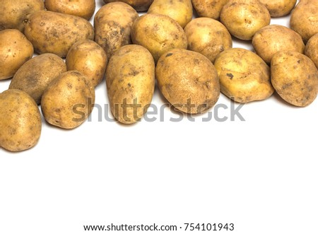 A lot of dirty potatoes on a white background. Potatoes scattered on a white background