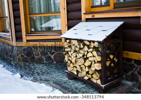 A lot of firewood stacked evenly in the yard for winter - stock photo